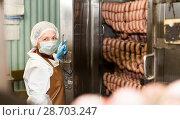 Купить «Woman checking sausages in baking machine», фото № 28703247, снято 11 июня 2018 г. (c) Яков Филимонов / Фотобанк Лори