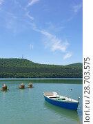 Купить «Синяя деревянная лодка для катания и домики-кормушки для водоплавающих птиц на озере Абрау», фото № 28703575, снято 12 июня 2018 г. (c) Наталья Гармашева / Фотобанк Лори
