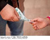 Men's and children's hand with Russian banknotes. Transfer of money. Стоковое фото, фотограф Элина Гаревская / Фотобанк Лори
