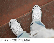 Купить «Legs in white sneakers and ripped jeans on the step of a red stone. The view from the top.», фото № 28703699, снято 7 июля 2018 г. (c) Элина Гаревская / Фотобанк Лори