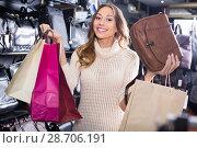 Купить «Young positive woman buying leather purse in shop», фото № 28706191, снято 24 сентября 2018 г. (c) Яков Филимонов / Фотобанк Лори