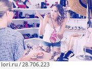 Купить «Young female is outraged at the price of sandals», фото № 28706223, снято 17 августа 2017 г. (c) Яков Филимонов / Фотобанк Лори