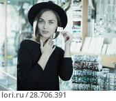 Купить «Adult woman customer in hat trying earrings», фото № 28706391, снято 16 октября 2017 г. (c) Яков Филимонов / Фотобанк Лори