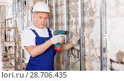 Купить «Construction worker using screw gun for aluminum profile mounting at indoors building site», фото № 28706435, снято 28 мая 2018 г. (c) Яков Филимонов / Фотобанк Лори