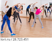 Купить «Teenage boys and girls with trainer stretching in dance hall», фото № 28723451, снято 26 апреля 2017 г. (c) Яков Филимонов / Фотобанк Лори