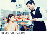 Attractive girl served by waiter, enjoying dinner in fish restau. Стоковое фото, фотограф Яков Филимонов / Фотобанк Лори