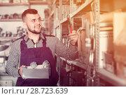 Купить «Worker showing his constructing tools at workplace», фото № 28723639, снято 15 марта 2017 г. (c) Яков Филимонов / Фотобанк Лори