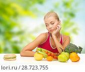Купить «doubting woman with fruits looking at hamburger», фото № 28723755, снято 23 марта 2013 г. (c) Syda Productions / Фотобанк Лори