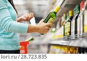 Купить «woman buying olive oil at supermarket or grocery», фото № 28723835, снято 2 ноября 2016 г. (c) Syda Productions / Фотобанк Лори