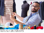 Купить «Male tailor working in the workshop on new designs», фото № 28728615, снято 12 апреля 2018 г. (c) Elnur / Фотобанк Лори