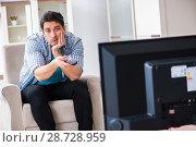 Купить «Man watching tv at home», фото № 28728959, снято 10 марта 2018 г. (c) Elnur / Фотобанк Лори