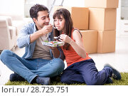 Купить «Young family eating food in new apartment after moving in», фото № 28729751, снято 6 декабря 2017 г. (c) Elnur / Фотобанк Лори