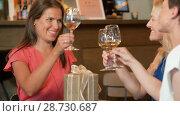 Купить «women giving present to friend at wine bar», видеоролик № 28730687, снято 4 июля 2018 г. (c) Syda Productions / Фотобанк Лори