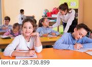 Купить «Portrait of young teacher woman at lesson with diligent school kids», фото № 28730899, снято 28 января 2018 г. (c) Яков Филимонов / Фотобанк Лори