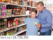 Купить «Smiling father and son looking goods with shopping list in store», фото № 28738355, снято 4 июня 2018 г. (c) Яков Филимонов / Фотобанк Лори