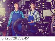 Купить «Mechanics working with new tires», фото № 28738451, снято 21 июля 2018 г. (c) Яков Филимонов / Фотобанк Лори