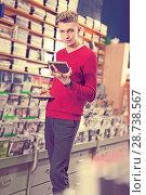 Купить «guy looking on box of DVD movie», фото № 28738567, снято 15 февраля 2018 г. (c) Яков Филимонов / Фотобанк Лори