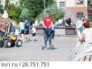 Купить «Tyumen, Russia, on July 15, 2018: the teenage boy rides a giroskuter in the summer on the square», фото № 28751751, снято 15 июля 2018 г. (c) Землянникова Вероника / Фотобанк Лори
