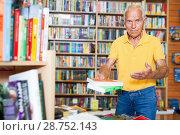 Купить «Intelligent older man holding out books to somebody while standing near racks», фото № 28752143, снято 11 июня 2018 г. (c) Яков Филимонов / Фотобанк Лори