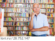 Купить «man looking focused and thoughtful while visiting bookshop», фото № 28752147, снято 11 июня 2018 г. (c) Яков Филимонов / Фотобанк Лори