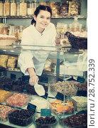 Купить «Woman showing tasty and useful sweets», фото № 28752339, снято 22 марта 2017 г. (c) Яков Филимонов / Фотобанк Лори