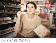 Купить «positive woman customer deciding on compact powder in shop», фото № 28752435, снято 21 февраля 2017 г. (c) Яков Филимонов / Фотобанк Лори