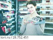 Купить «happy female customer deciding on make-up items in cosmetics shop», фото № 28752451, снято 21 февраля 2017 г. (c) Яков Филимонов / Фотобанк Лори