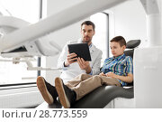 Купить «dentist showing tablet pc to kid patient at clinic», фото № 28773559, снято 22 апреля 2018 г. (c) Syda Productions / Фотобанк Лори