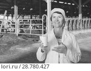 Купить «Confident senior woman veterinarian approvingly demonstrating milk on dairy farm», фото № 28780427, снято 24 октября 2017 г. (c) Яков Филимонов / Фотобанк Лори