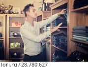 Купить «Brunette man deciding on new trousers», фото № 28780627, снято 28 марта 2017 г. (c) Яков Филимонов / Фотобанк Лори