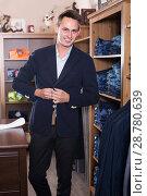 Купить «Customer examining suits», фото № 28780639, снято 28 марта 2017 г. (c) Яков Филимонов / Фотобанк Лори