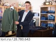 Купить «Guy shopper choosing new jacket in men's store», фото № 28780643, снято 28 марта 2017 г. (c) Яков Филимонов / Фотобанк Лори