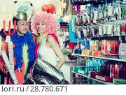 Купить «Cheerful couple trying on helmet with horns», фото № 28780671, снято 11 апреля 2017 г. (c) Яков Филимонов / Фотобанк Лори