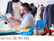 Купить «Male tailor working in the workshop on new designs», фото № 28781543, снято 12 апреля 2018 г. (c) Elnur / Фотобанк Лори