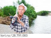 Купить «Mature fisherman with rod at riverside», фото № 28791083, снято 10 июня 2018 г. (c) Яков Филимонов / Фотобанк Лори
