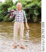 Купить «Fisherman posing with catch at riverside», фото № 28791099, снято 10 июня 2018 г. (c) Яков Филимонов / Фотобанк Лори