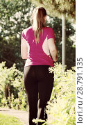 Smiling adult woman in pink T-shirt is jogging back. Стоковое фото, фотограф Яков Филимонов / Фотобанк Лори