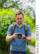 Купить «young boy takes on the camera in the park», фото № 28803731, снято 28 июня 2018 г. (c) Иван Карпов / Фотобанк Лори