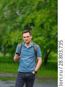 Купить «young man using mobile phone in the forest while hiking», фото № 28803735, снято 28 июня 2018 г. (c) Иван Карпов / Фотобанк Лори