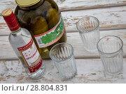 """Бутылка водки """"Праздничная"""", три граненных стакана и банка с солеными огурцами лежат на деревянном столе (2018 год). Редакционное фото, фотограф Николай Винокуров / Фотобанк Лори"""