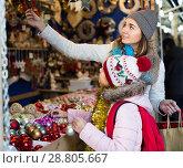 Купить «glad mother with little daughter buying decorations for Xmas», фото № 28805667, снято 21 сентября 2018 г. (c) Яков Филимонов / Фотобанк Лори