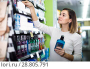 Купить «interested girl customer looking for effective mouthwash in supermarket», фото № 28805791, снято 23 ноября 2016 г. (c) Яков Филимонов / Фотобанк Лори