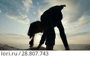 Купить «Young woman doing acro yoga on the large stone at sunrise», видеоролик № 28807743, снято 17 октября 2018 г. (c) Константин Шишкин / Фотобанк Лори
