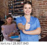 Купить «Young smiling girl manicurist standing in modern nail salon», фото № 28807843, снято 30 мая 2018 г. (c) Яков Филимонов / Фотобанк Лори