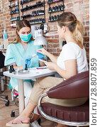 Купить «Professional manicurist in mask doing manicure by nail to girl», фото № 28807859, снято 30 мая 2018 г. (c) Яков Филимонов / Фотобанк Лори