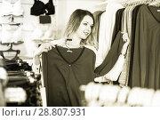 Купить «Female customer is choosing pretty long sleeve shirt», фото № 28807931, снято 20 марта 2017 г. (c) Яков Филимонов / Фотобанк Лори
