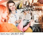 Купить «Female seller demonstrating client bras in underwear store», фото № 28807947, снято 20 марта 2017 г. (c) Яков Филимонов / Фотобанк Лори