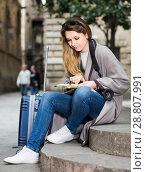 Купить «traveling girl searching for the direction using a booklet in the town», фото № 28807991, снято 27 марта 2017 г. (c) Яков Филимонов / Фотобанк Лори