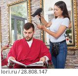 Купить «Young woman hairstylist drying hair with blow dryer of guy», фото № 28808147, снято 25 апреля 2018 г. (c) Яков Филимонов / Фотобанк Лори