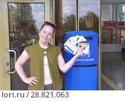 Женщина стоит у почтового ящика с открытками в руках (2017 год). Редакционное фото, фотограф Мартынов Антон / Фотобанк Лори